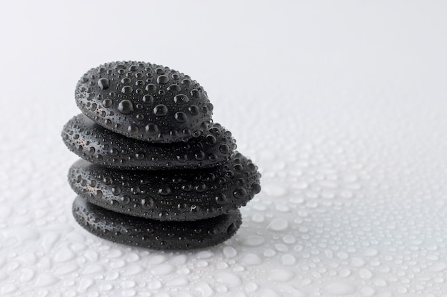 Stacked black stones on white background
