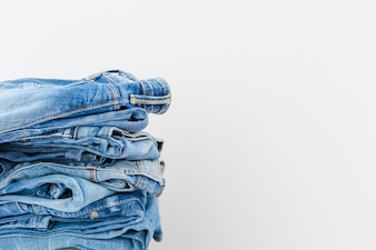 Stacked blue jeans on white background