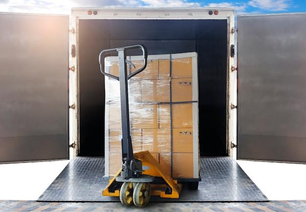 선적 컨테이너에 적재되는 팔레트 랙에 쌓인 판지 상자. 화물 선적 상자, 도로화물 트럭, 창고. 물류 및 운송.