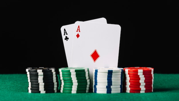 Stacked casino chips in front of two aces on poker table