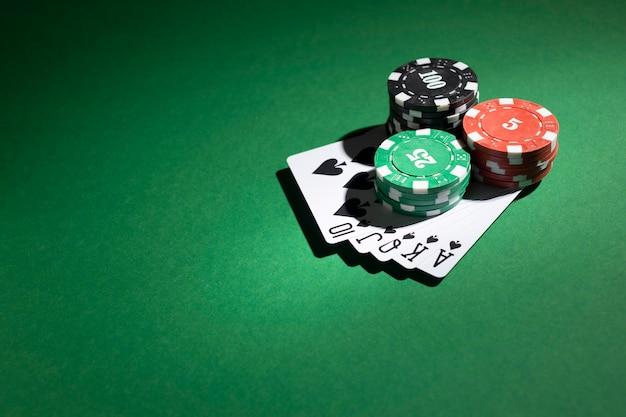 積み重ねられたカジノトークンと緑の背景にロイヤルフラッシュ