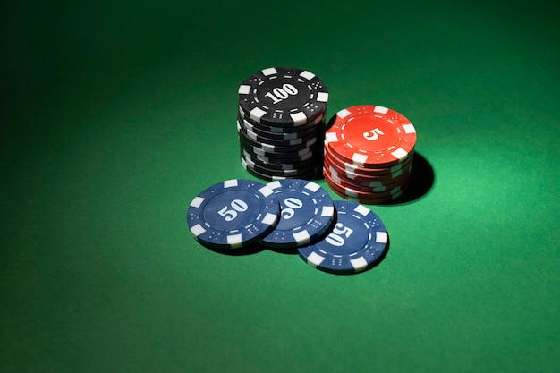 Сложенные жетоны казино на зеленом фоне
