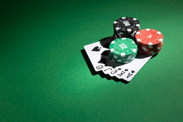Stacked casino tokens and royal flush on green background