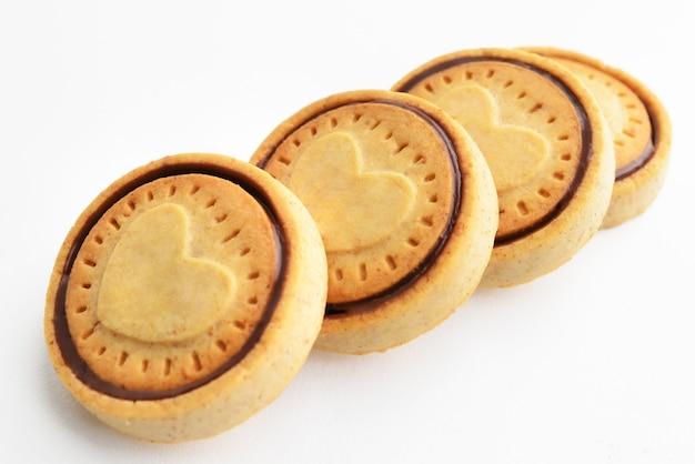 積み上げチョコチップクッキー。象徴的なイメージ。おいしいおやつのコンセプト。甘いデザート。白色の背景。セレクティブフォーカス。閉じる。クッキーハートの形。