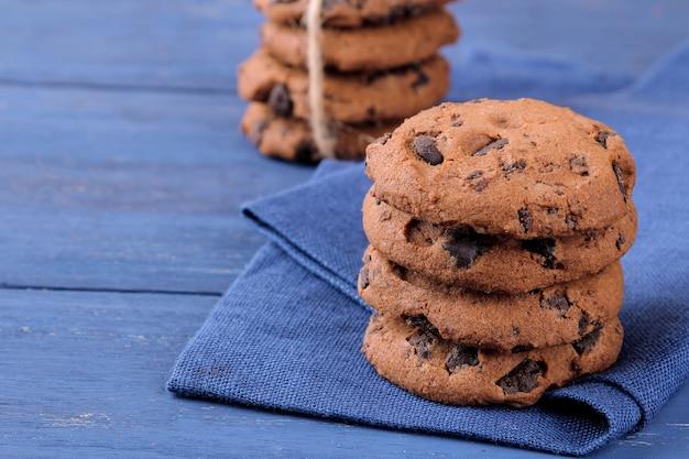 青い木製のテーブルの上の美しいナプキンに積み重ねられたチョコレートクッキー。焼く。うまい