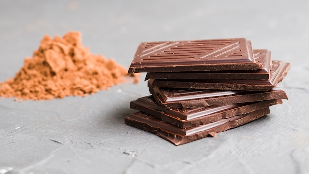 Stacked chocolate pieces next to cocoa powder
