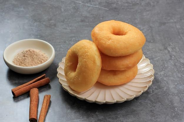 누적된 계피 도넛, 계피 설탕 더스트와 함께 신선한 튀긴 도넛. 소박한 접시, 회색 시멘트 테이블에 제공