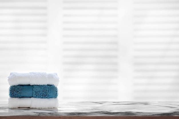 Stacked clean spa towels on marble top table.