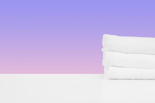 色の背景に対して白いテーブルにきれいなタオルを積み重ねた