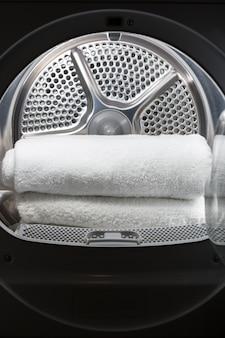 開いた洗濯機のドラムの中に積み重ねられたきれいな白いタオル