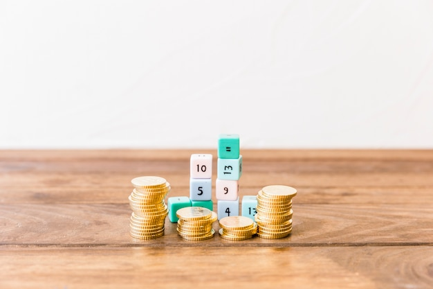 Stacked coins and math blocks on wooden tabletop