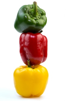 Stacked of colorful green , red and yellow bell peppers paprika on white background