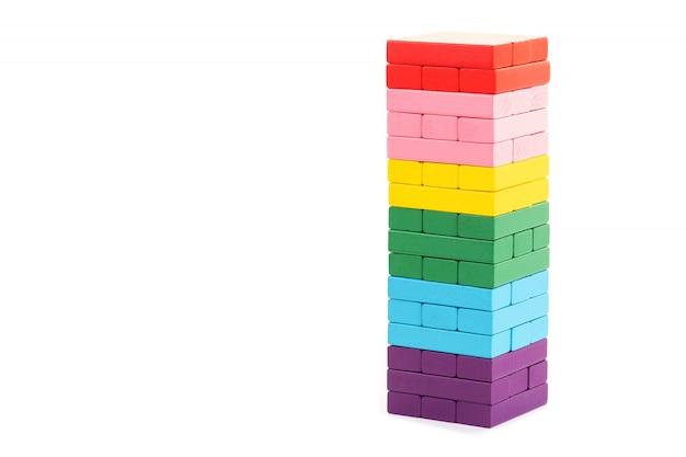 白い背景の上の積み上げカラフルな木製ブロックおもちゃ
