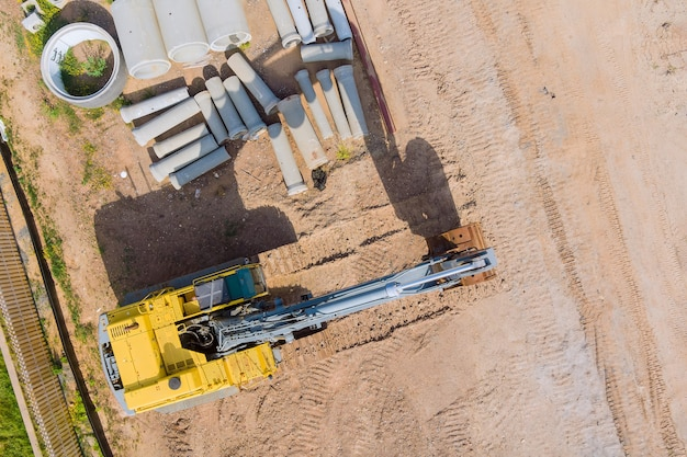 小さな掘削機の建設現場のアパートの建物に積み上げられたコンクリート排水下水管