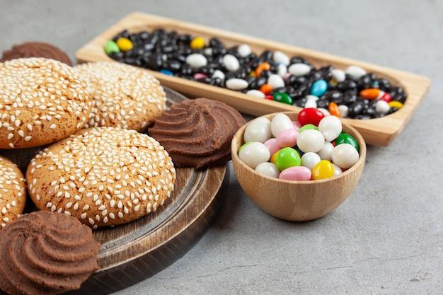 Сложенное печенье на деревянной доске рядом с кучей конфет в миске и деревянным подносом на мраморной поверхности