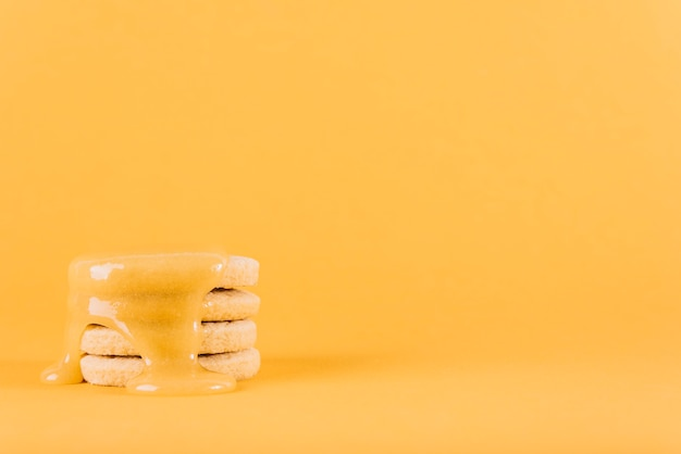 Stacked cookies with lemon curd on yellow background