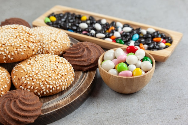 Stacked cookies on wooden board next to piles of candies in a bowl and a wooden tray on marble surface