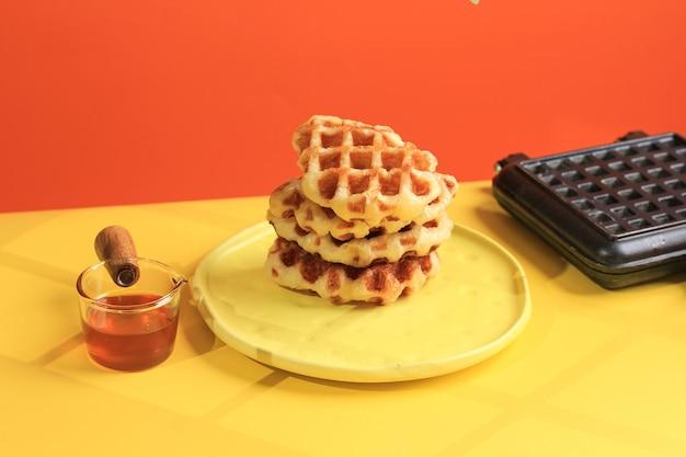 黄色のテーブルとオレンジ色の背景に積み上げクロワッサンワッフル。 croffleは韓国のバイラルケーキです。コンセプトポップカラーフード、テキスト用コピースペース