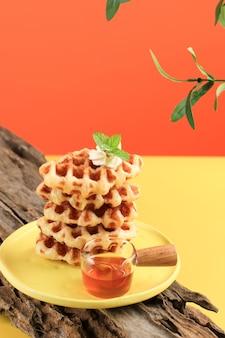黄色のテーブルとオレンジ色の背景に積み上げクロワッサンワッフル。 croffleは韓国のバイラルケーキです。コンセプトポップカラーフード