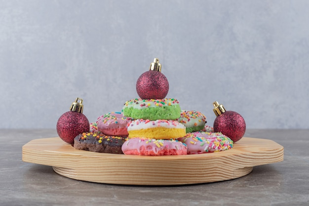 Stacked donuts and christmas baubles on a wooden platter on marble surface
