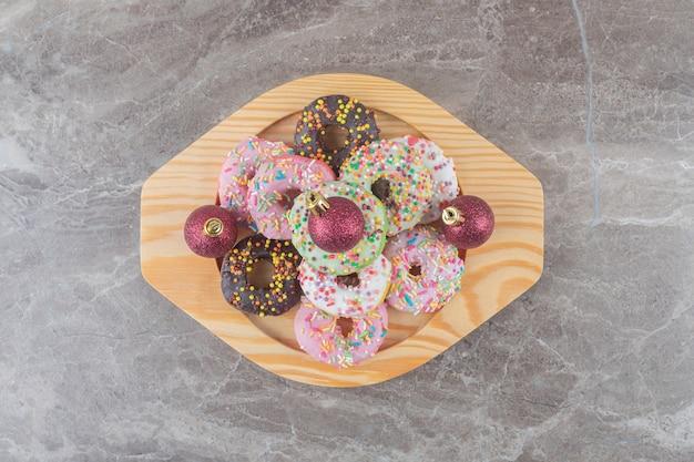 Ciambelle impilate e palline di natale su un piatto di legno su una superficie di marmo