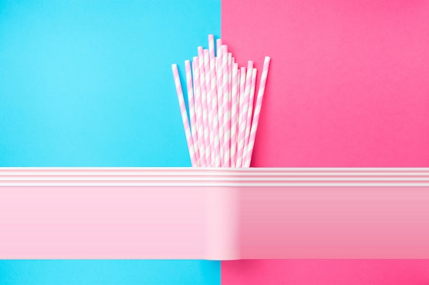 Stacked drinking paper cups with striped straws on duo tone blue pink background.