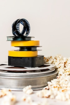 Stacked of film reels with film strip near the popcorn against white background