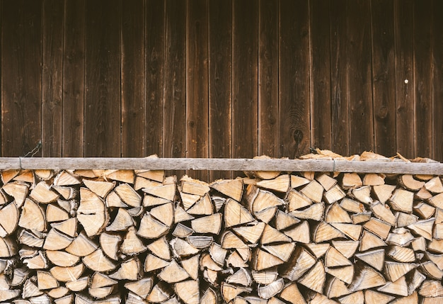 Stacked firewood in front of a wooden hut in the bavarian alps.