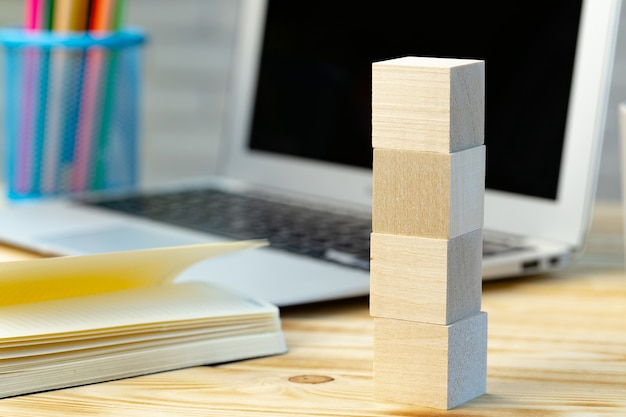 Stacked four wooden blocks on working desk with open laptop and book