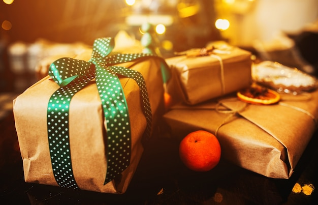 Stacked gifts with green bows and an orange