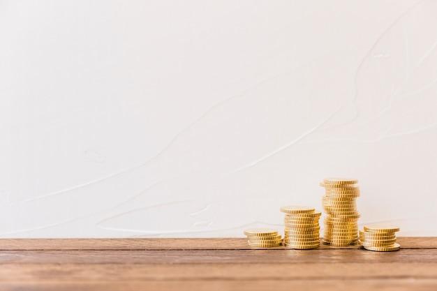 Сложенные золотые монеты перед стеной