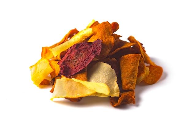흰색으로 격리된 야채 말린 감자, 당근, 비트 칩의 누적된 힙