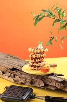 黄色の背景に積み上げられた自家製クロワッサンワッフル(クロワッフル)。ハチミツまたはメープルシロップを添えて