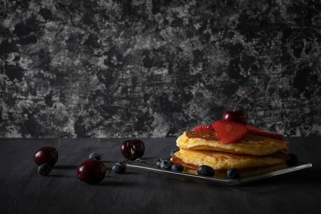 빈티지 블랙 나무 테이블에 체리 딸기와 블루베리를 얹은 뜨거운 케이크