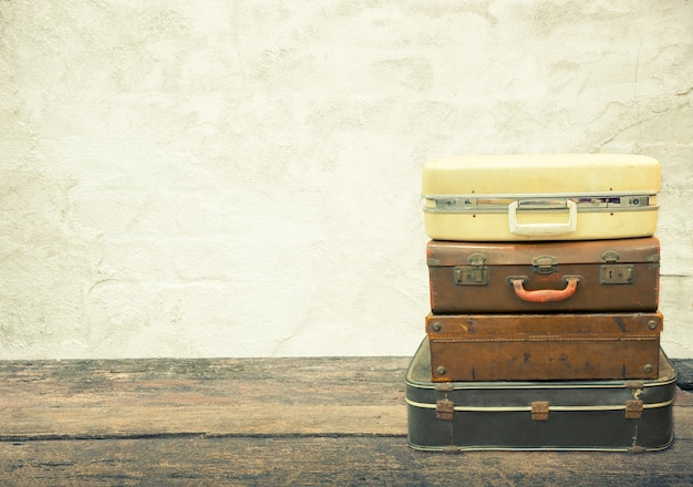 Stacked leather luggage on wood plank with old concrete background. travel concept.