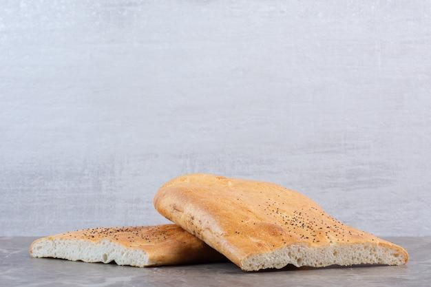 Stacked loaves of crisp half-sliced tandoori bread on marble.