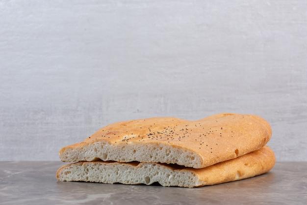 Stacked loaves of half-sliced tandoori bread on marble.