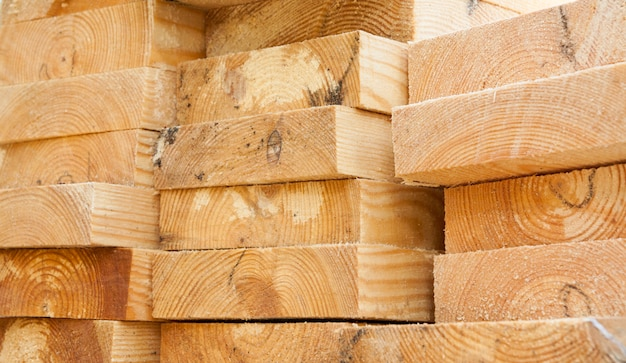 Stacked of lumber in timber logs for construction or industrial work. wooden building materials