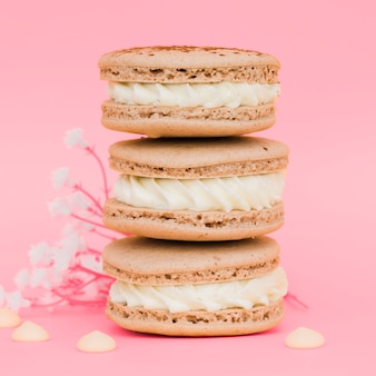 Stacked of macaroons with flowers against pink background