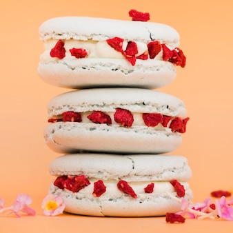 Stacked of macaroons with flowers against pink colored background