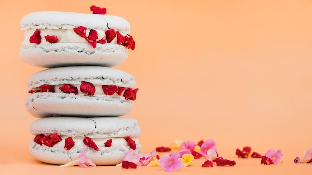 Stacked of macaroons with flowers on beige background