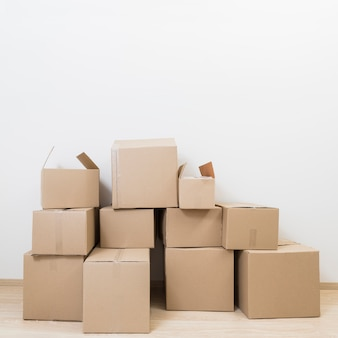 Stacked of moving cardboard boxes against white wall