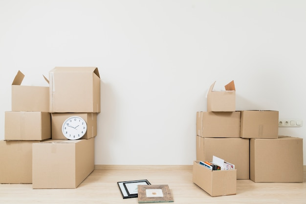 Stacked of moving cardboard boxes with clock and picture frame against white wall