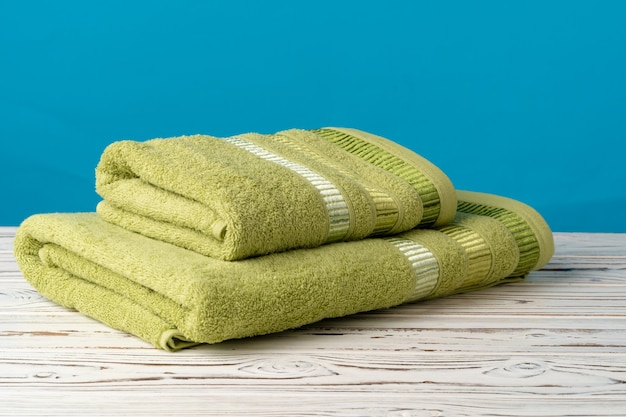 Сложенные новые полотенца на деревянном столе