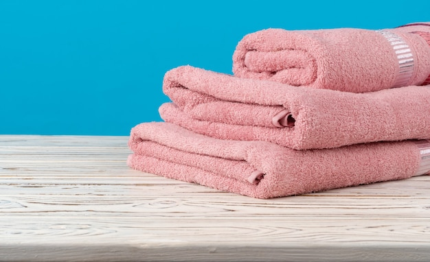 Stacked new towels on a wooden table