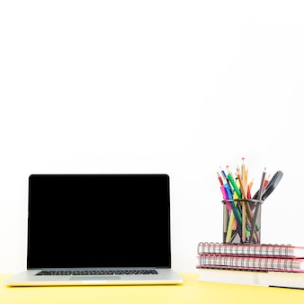 Stacked notebook with various pens and pencils in holder near laptop on desk