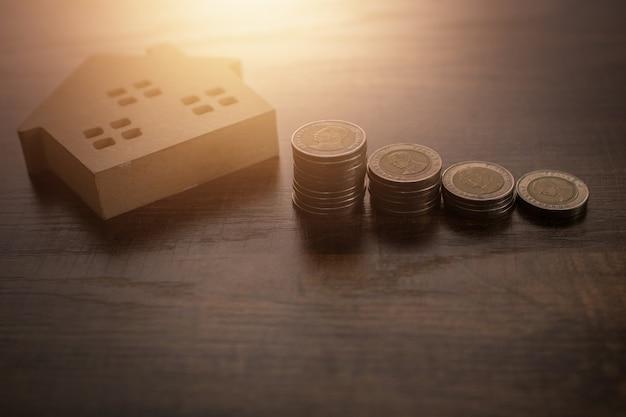 木製のテーブル、住宅ローン、不動産のコンセプトに木製の家のモデルで成長しているお金のコインの積み重ね