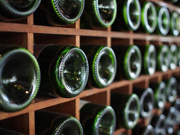 Сложены старые бутылки вина в подвале