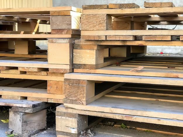 Сложенные старые использованные деревянные поддоны на улице