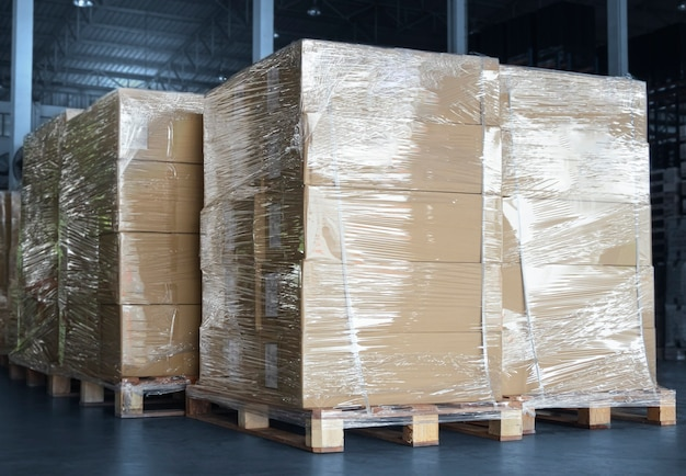 Stacked of package boxes wrapped plastic flim on pallets at storage warehouse shipment boxes